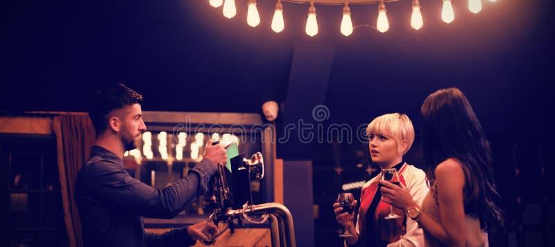Barman agissant l'un sur l'autre avec de belles femmes au compteur photographie stock libre de droits