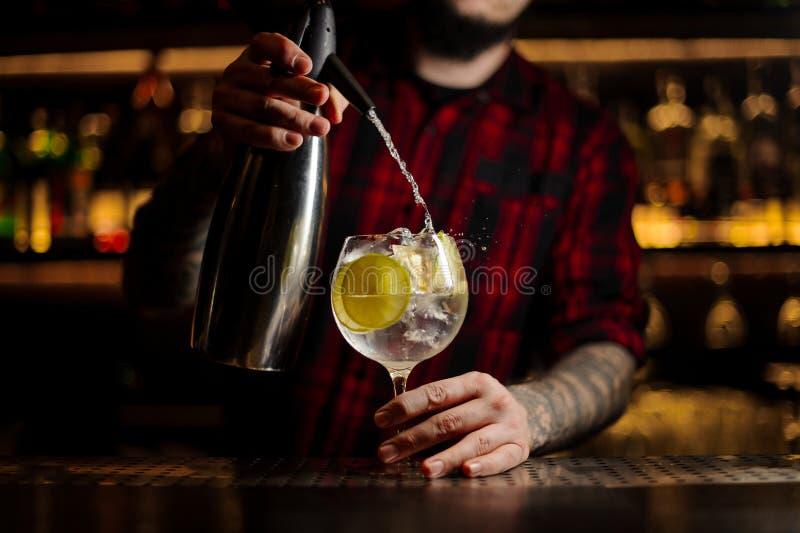 Barman ajoutant l'eau tonique au au verre de cocktail plein o photo stock