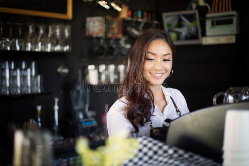 Barman asiatique de femmes souriant et à l'aide de la machine de café en café s images stock
