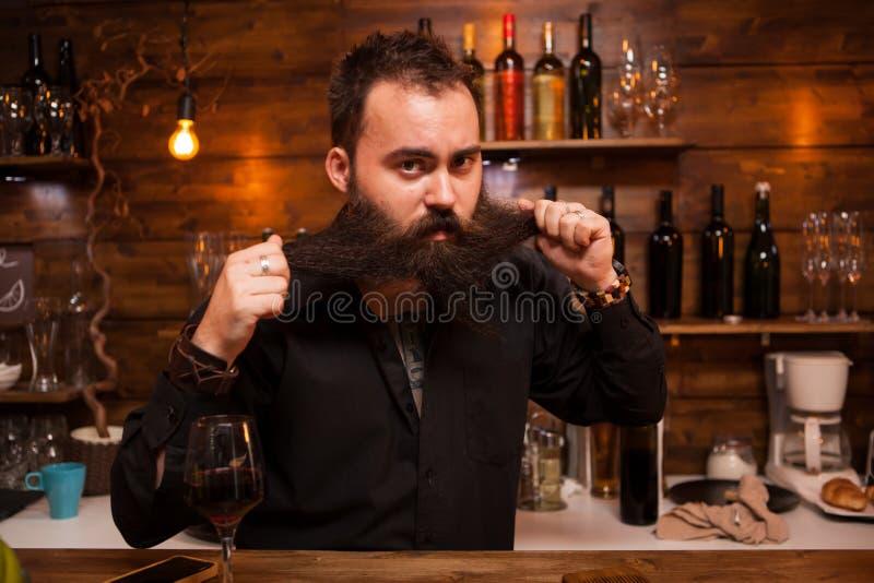 Barman atrativo que joga com sua barba longa atr?s do contador fotografia de stock