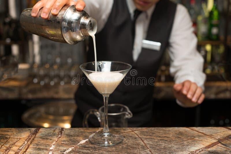 Barman au travail, préparant des cocktails colada de versement de pina au verre de cocktail images libres de droits