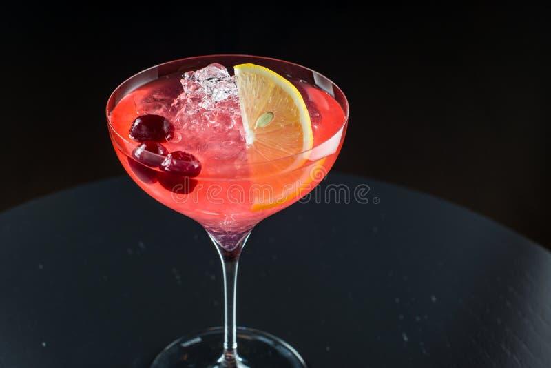 Barman au travail, préparant des cocktails versement cosmopolite au verre de cocktail image libre de droits