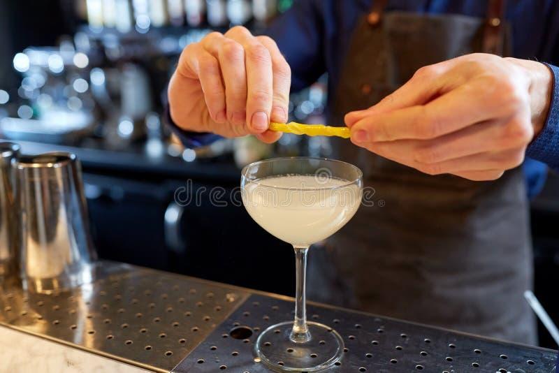 Barman avec le verre du cocktail et du citron à la barre images stock