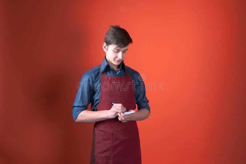 Barman avec les cheveux foncés dans l'écriture rouge de tablier dans le carnet avec le stylo et sur le fond colal avec l'espace d images stock