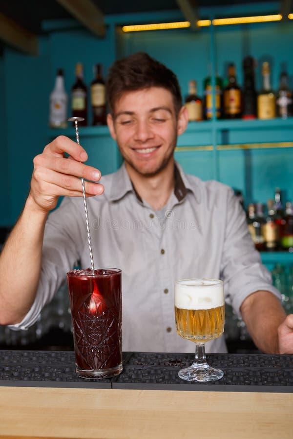 Barman in bar de binnenlandse het maken cocktail van de alcoholbes stock foto's