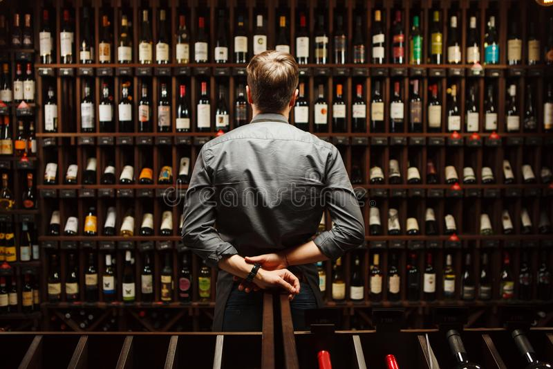 Barman bij het hoogtepunt van de wijnkelder van flessen met uitstekende dranken stock foto's