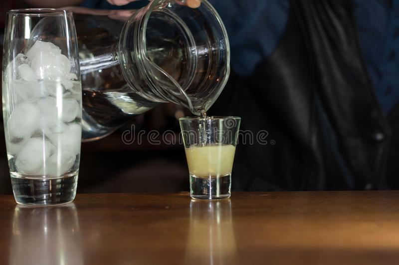 Barman bij tegen gietende soda van kruik in glas met sap stock foto's