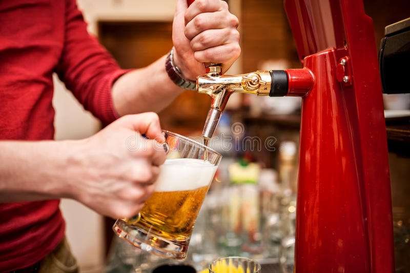 Barman brewing a draft, unfiltered beer at pub royalty free stock photo