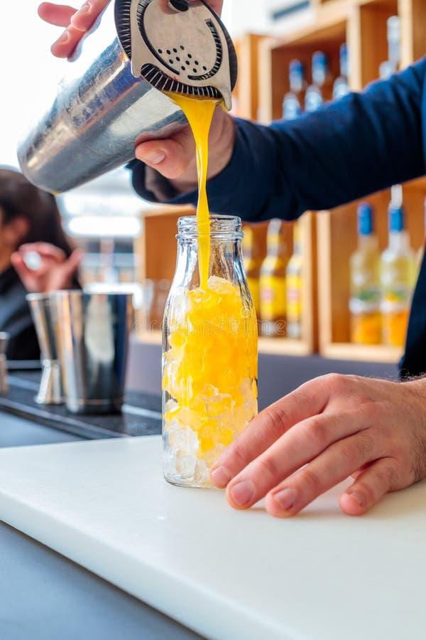 Barman che versa un cocktail arancione in una bottiglia di vetro con fondo sfocato fotografia stock libera da diritti