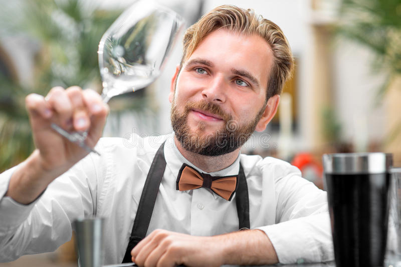 Barman checking the cleanliness of glass. Elegant barman checking the cleanliness of glass at the restaurant stock photo