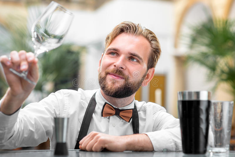 Barman checking the cleanliness of glass. Elegant barman checking the cleanliness of glass at the restaurant royalty free stock photo
