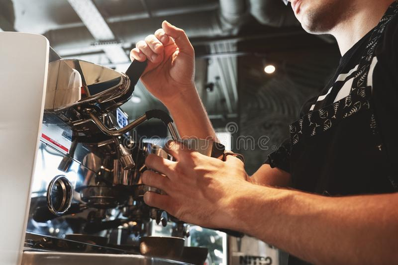 Barman cuisant le lait à la vapeur en moussant le broc utilisant le cappuccinator professionnel de machine de café en café photo stock
