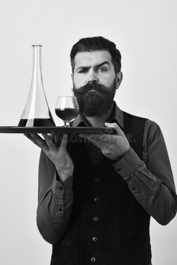 Barman with curious face serves scotch or brandy. Waiter with glass and bottle of whiskey on tray. royalty free stock photos