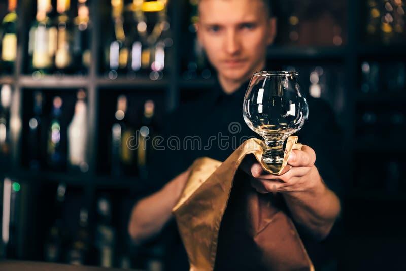 Barman czyści szkło z płótnem przy baru kontuaru tłem Barman czyści szkło na barze obraz stock