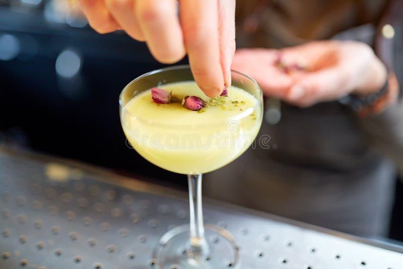 Barman décorant le cocktail en verre à la barre image stock