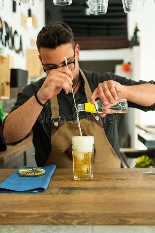 Barman dans le bar ou le restaurant préparant un cocktail tonique de genièvre image libre de droits