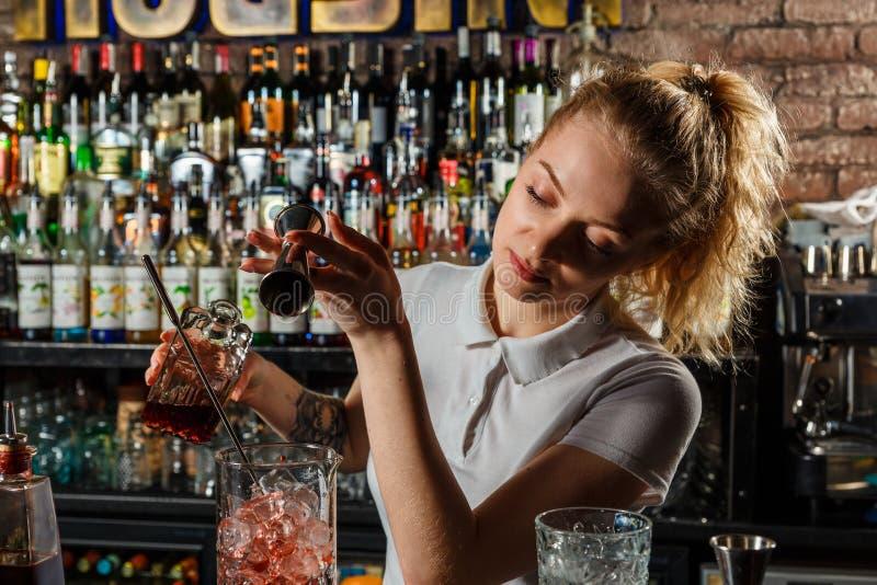 Barman de femme faisant un cocktail d'alcool images stock