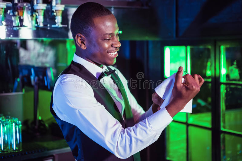 Barman de sorriso que limpa um vidro fotografia de stock royalty free