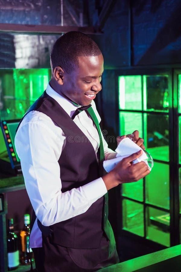 Barman de sorriso que limpa um vidro foto de stock royalty free