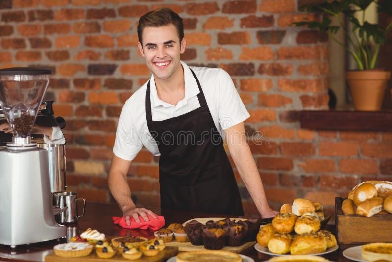 Barman de sourire nettoyant le compteur photo libre de droits