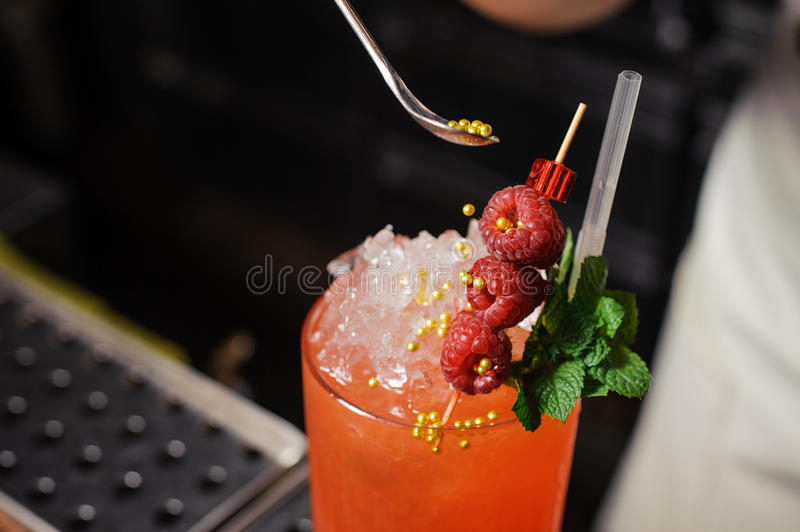 Barman is decorating cocktail with rasberry stock photography