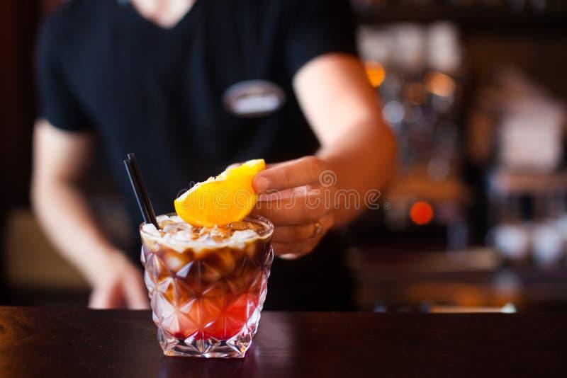 Barman dekoruje koktajl z slise pomarańcze przy noc klubem C zdjęcie royalty free