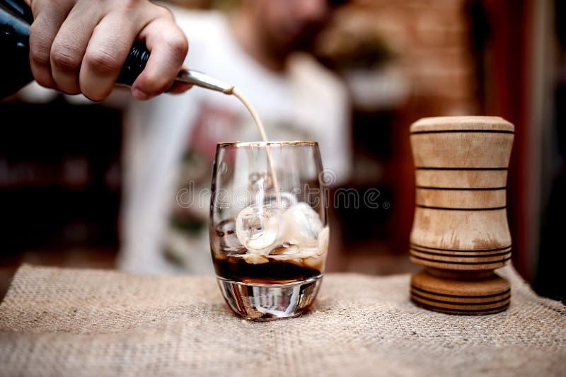 Barman die alcoholische alcoholische drank in klein glas op de teller gieten royalty-vrije stock foto's