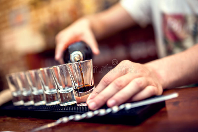 Barman die bruine alcoholische cocktail in glazen giet royalty-vrije stock afbeelding