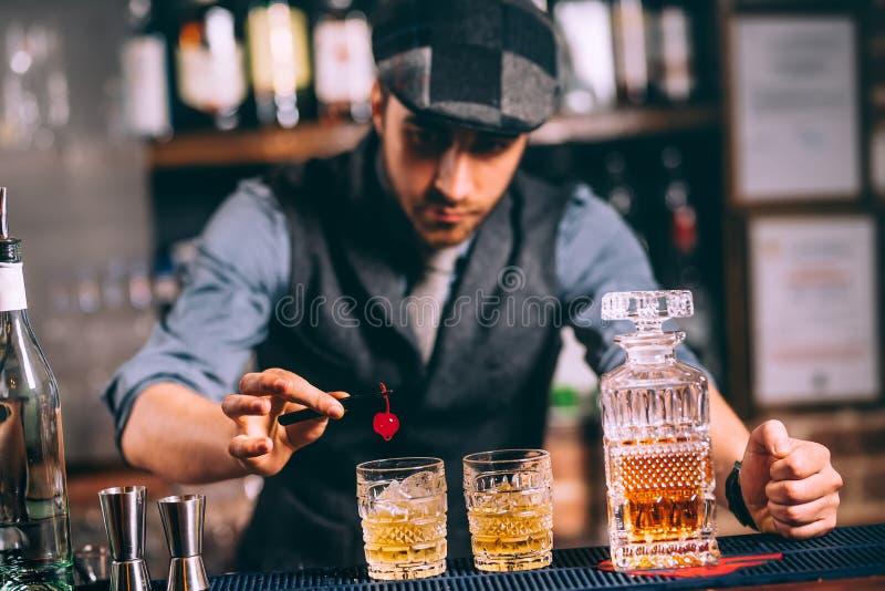 Barman die dranken en whiskycocktails versieren bij moderne bar royalty-vrije stock fotografie