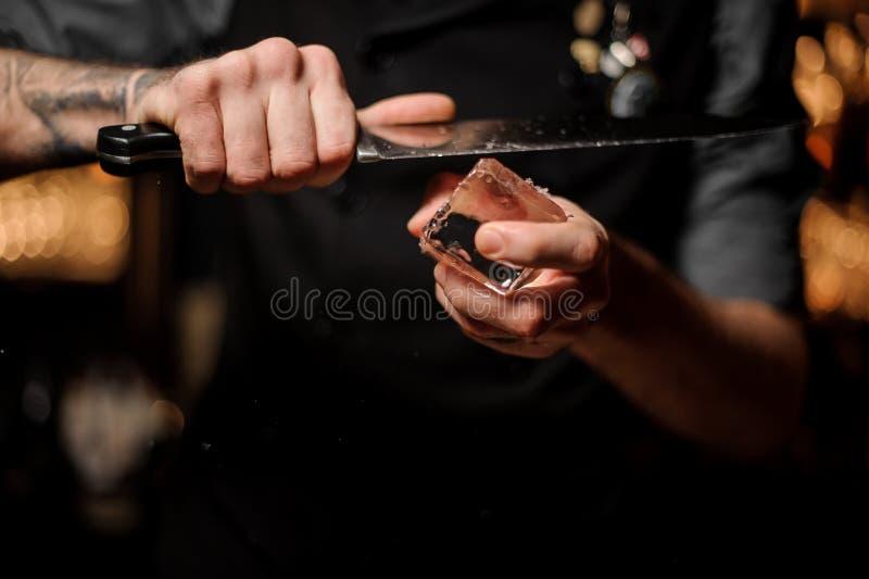 Barman die een groot ijsblokje met een mes snijden stock afbeelding