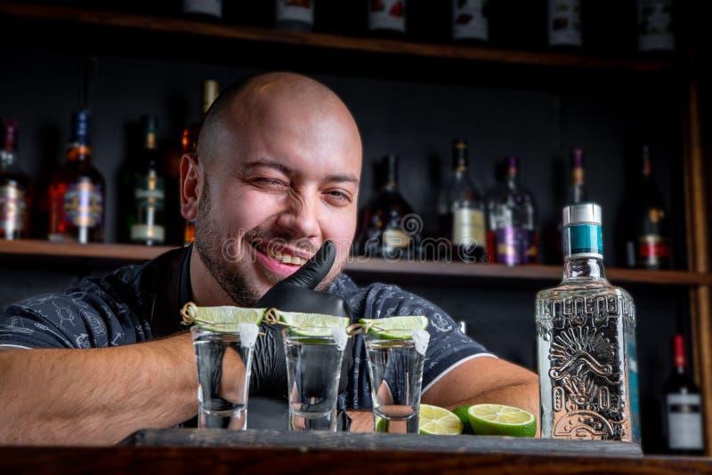 Barman die harde geest gieten in kleine glazen zoals alcoholische schoten van tequila of sterke drank stock fotografie