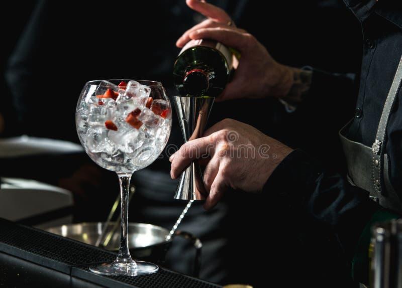 Barman die het verfrissen coctail met aardbeien geïsoleerd o maken zich royalty-vrije stock fotografie