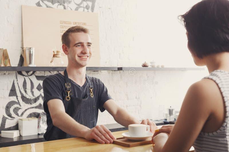 Barman die met de gast en de dienende koffie babbelen stock foto