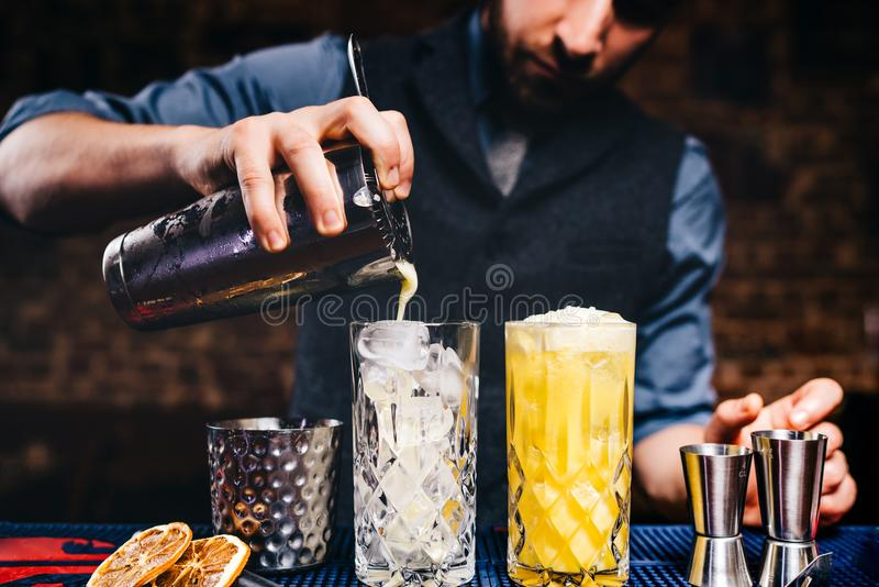 Barman do vintage que derrama o cocktail alaranjado fresco da vodca sobre o gelo nos produtos vidreiros de cristal foto de stock royalty free