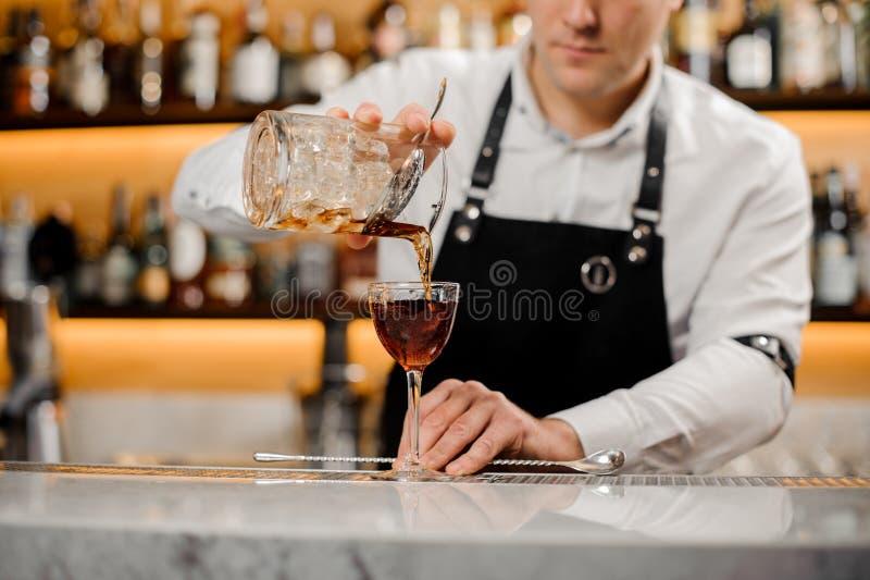 Barman dodaje alkoholicznego napój w eleganckiego szkło obraz royalty free