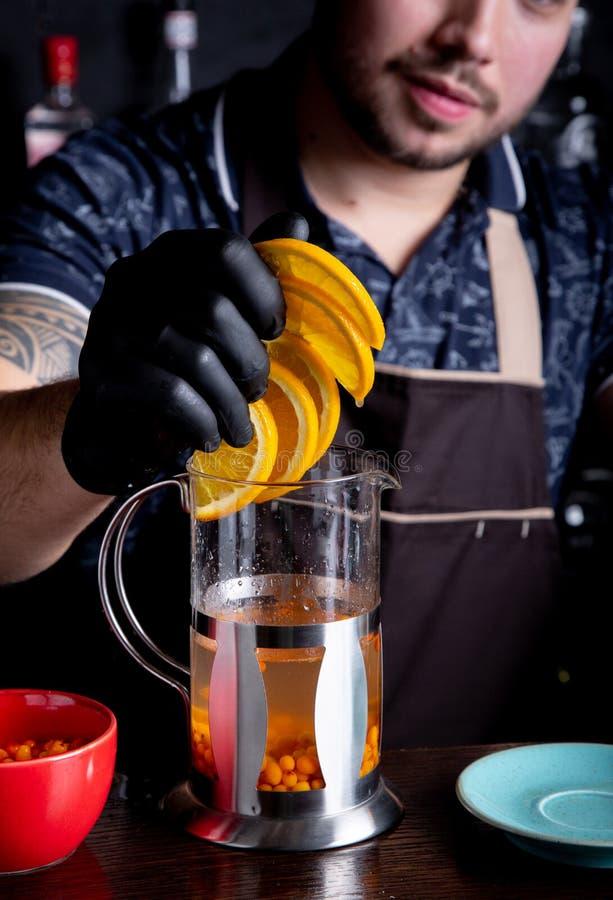 Barman dodaje pokrojonej pomarańcze herbata w górę fotografia stock