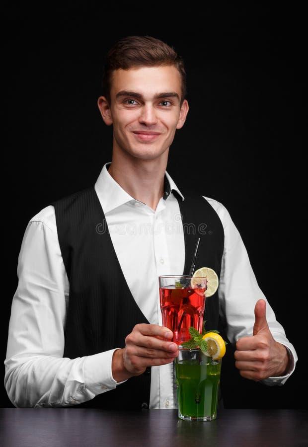 Barman elegante com bebidas alcoólicas coloridas em um fundo preto Empregado de bar com agitações frutados Conceito do serviço do fotografia de stock