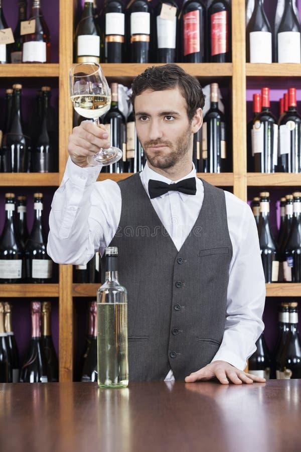 Barman Examining White Wine en verre à la boutique image libre de droits
