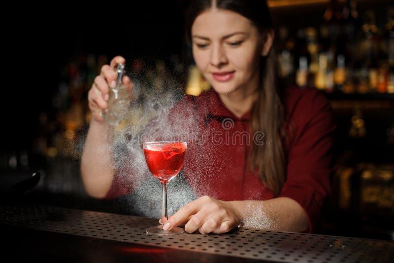 Barman féminin décorant un verre de cocktail alcoolique avec s image libre de droits