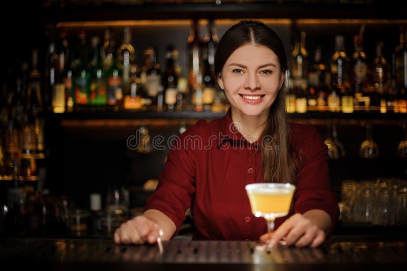 Barman féminin de sourire servant un cocktail jaune délicieux photographie stock libre de droits
