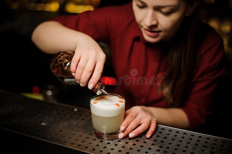 Barman féminin faisant une préparation finale à servir un cocktail blanc délicieux images stock