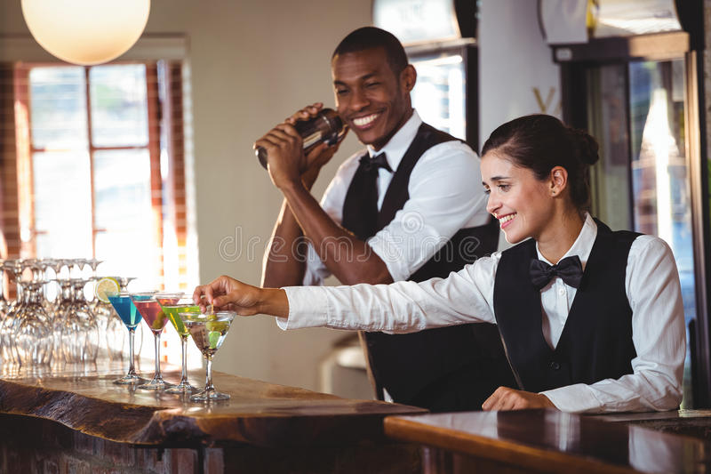 Barman féminin garnissant le cocktail avec l'olive photo stock