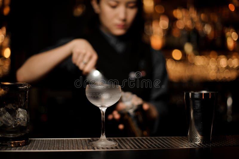Barman féminin préparant le cocktail utilisant le dispositif trembleur au compteur de barre images stock
