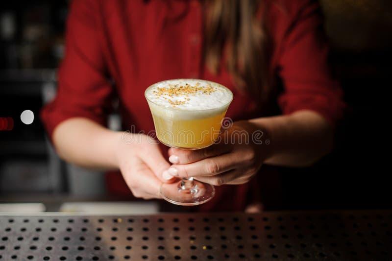 Barman féminin servant un cocktail jaune décoré délicieux image stock