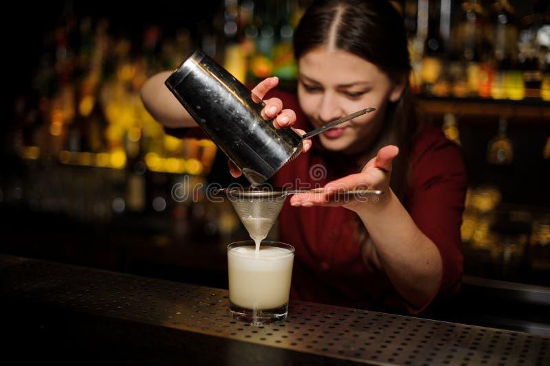 Barman féminin versant un cocktail du dispositif trembleur par le bluteur images libres de droits