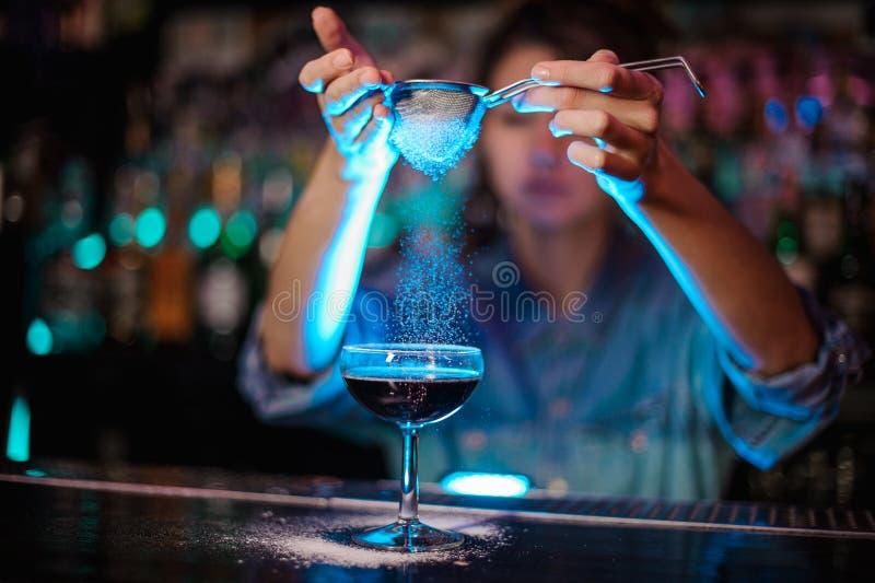 Barman fêmea que adiciona a um cocktail marrom um pó através do filtro na luz azul fotos de stock