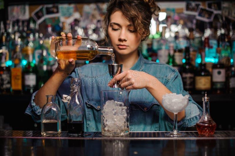 Barman fêmea que derrama ao jigger de aço uma bebida alcoólica fotos de stock
