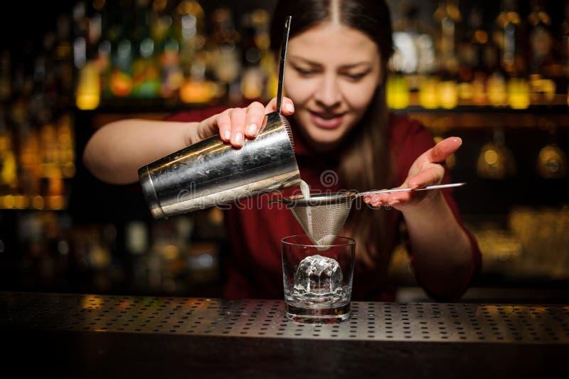 Barman fêmea que derrama para fora um cocktail do abanador através da peneira imagens de stock royalty free