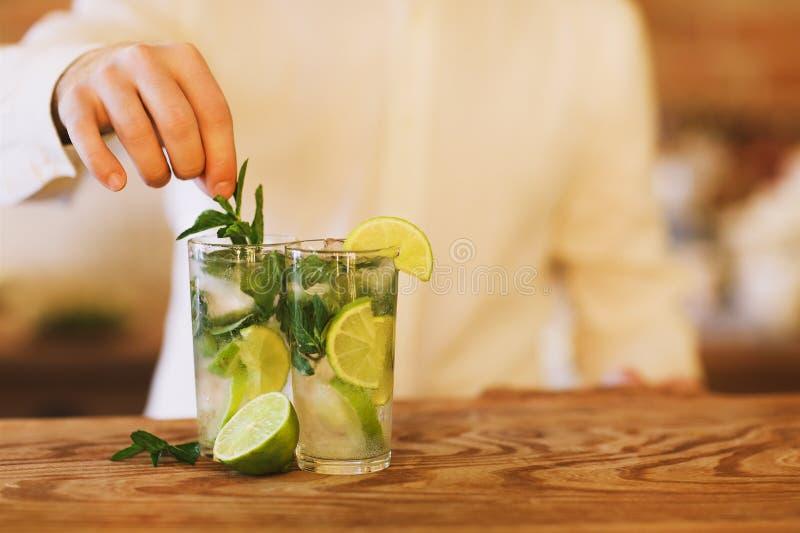 Barman faisant deux cocktails de mojito images stock