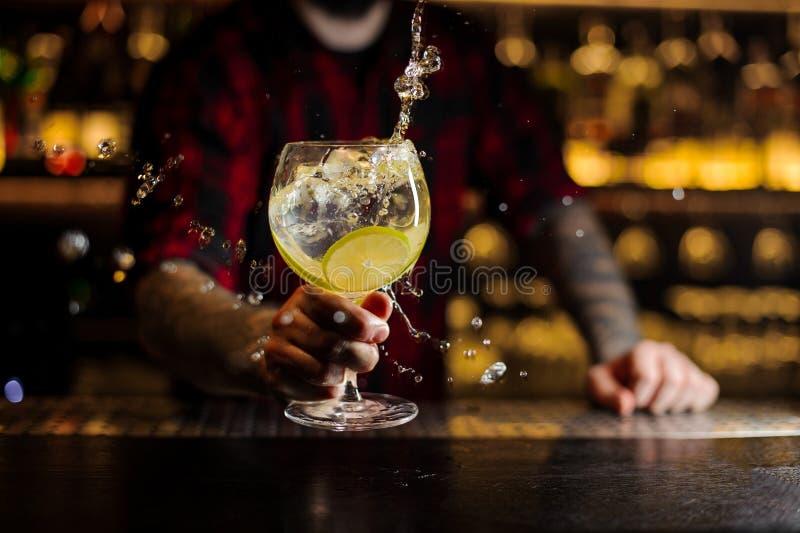 Barman faisant l'éclaboussure d'un cocktail délicieux de Gin Tonic avec l image stock
